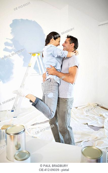 Couple hugging among paint supplies
