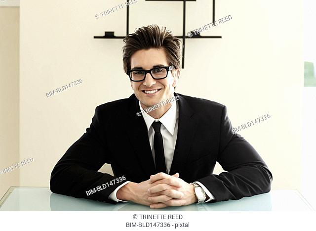 Trendy Caucasian businessman sitting at desk