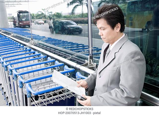 Side profile of a businessman reading a document and waiting outside an airport