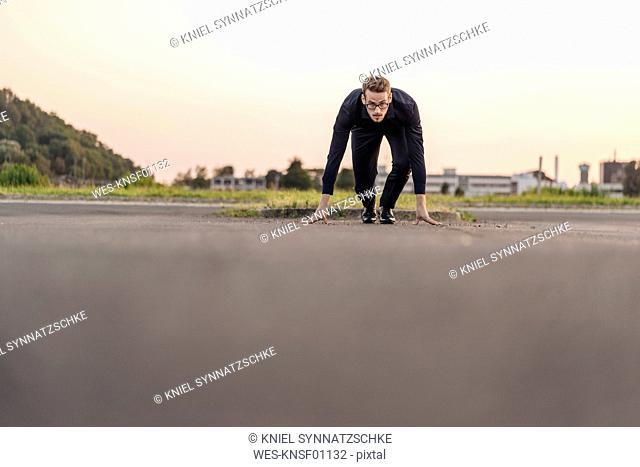 Businessman starting race on road