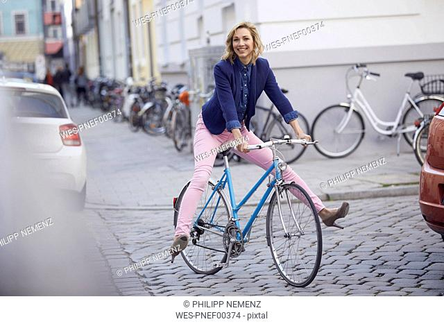 Blond woman riding a bike in the city