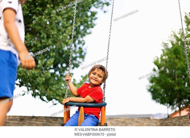 Portrait of happy little boy sitting on a swing