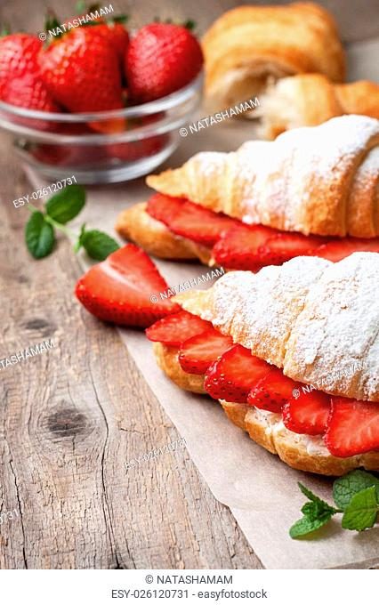 croissant with fresh strawberries, ricotta (cottage cheese) for breakfast on a wooden background