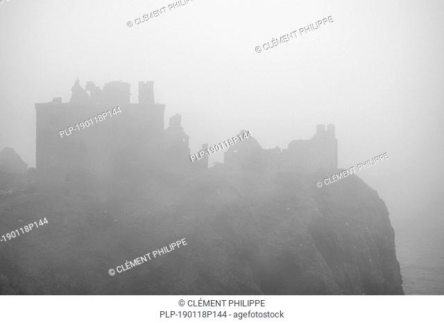 Dunnottar Castle in thick fog, ruined medieval fortress near Stonehaven on sea cliff along the North Sea coast, Aberdeenshire, Scotland, UK