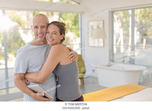Portrait happy mature couple with digital tablet hugging in bedroom