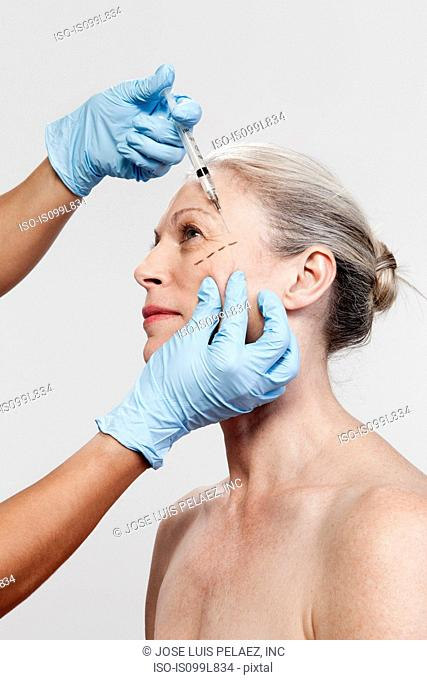 Mature woman receiving injections