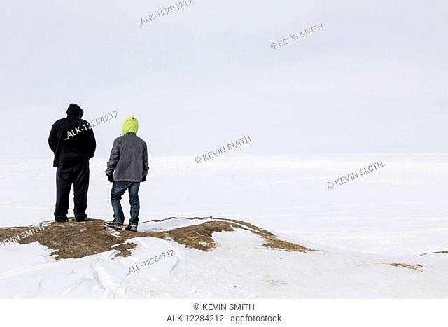 Two male tourists view the sea ice from the shore line on a cloudy overcast day, Barrow, North Slope, Arctic Alaska, USA, Winter