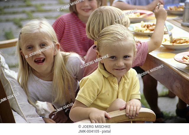 Five children, girls, 1-5 5-10 years old, sitting on a terrace in front of a house, having lunch
