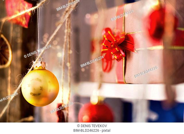 Ornaments hanging on string near gift box
