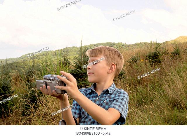 Young boy outdoors, looking at video camera