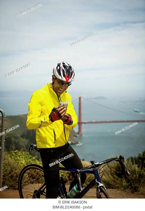 Hispanic man on bicycle texting on cell phone at waterfront