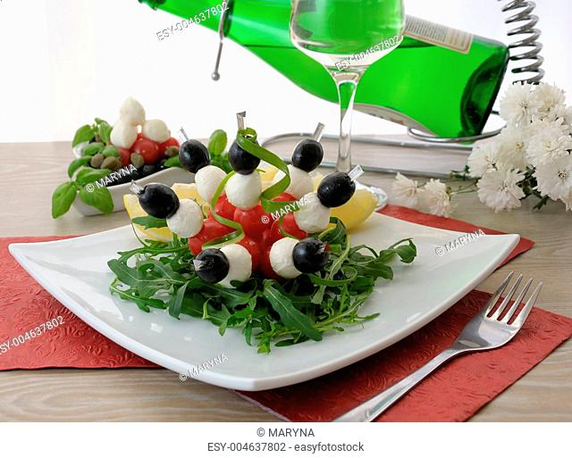 Appetizer of mozzarella, cherry tomatoes and olives with Arugula
