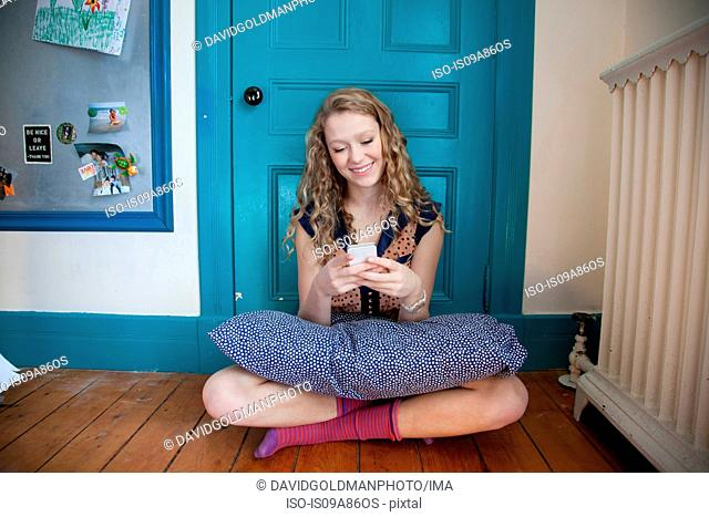 Teenager sitting in front of blue door, using mobile telephone