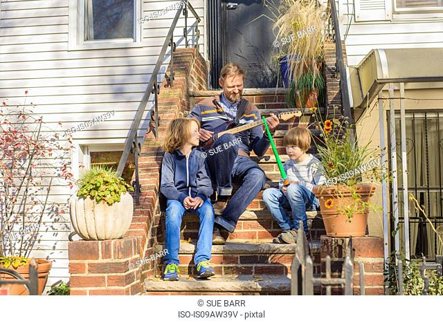 Father and sons sitting together on front steps, father playing guitar