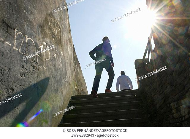 Stair at the entrance of the City Wall of Lugo, Galicia, Spain. Back lit image showing two people and a twinkle of the sun