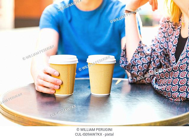 Cropped view of young couple sitting at table with disposable cups