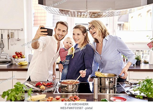 Happy family cooking in kitchen taking a selfie