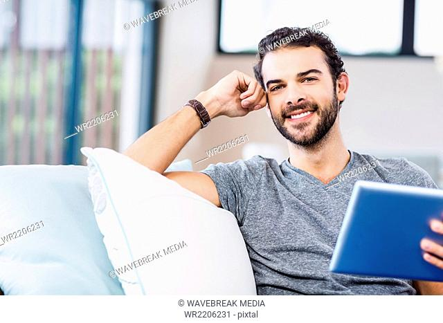 Handsome man using tablet smiling at camera
