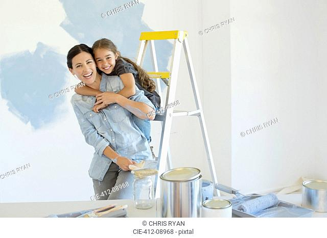 Portrait of mother and daughter hugging near paint supplies