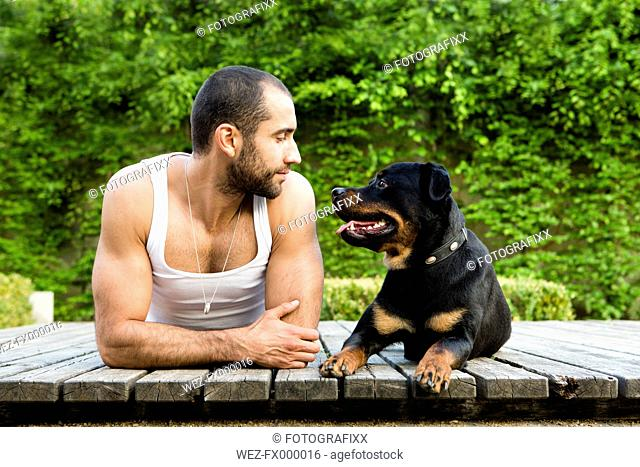 Portrait of young man face to face with his Rottweiler lying on boardwalk