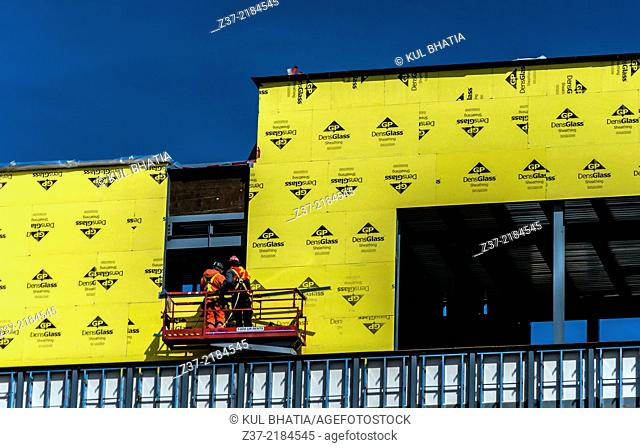 Workers install insulation on the outside of a building in progress, Ontario, Canada
