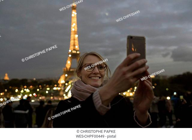 France, Paris, portrait of happy woman taking selfie with lighted Eiffel Tower in the background