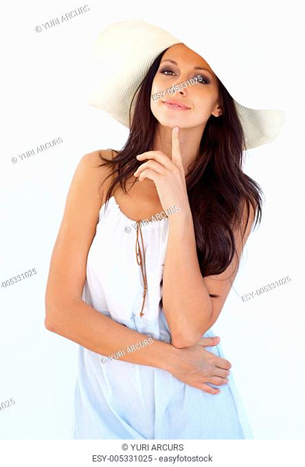 A stunning young woman in summer-wear thinking to herself