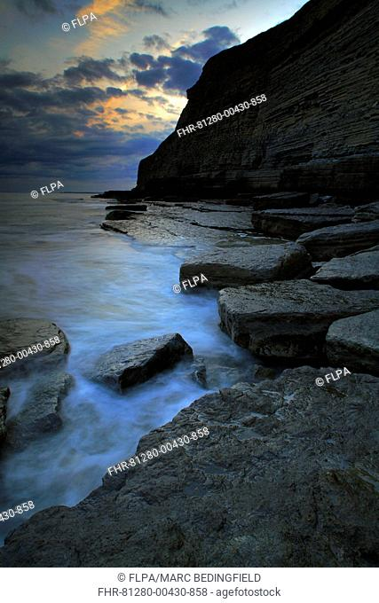 View of rock formations and cliffs in rugged bay at sunset, Dunraven Bay, Southerndown, Glamorgan Heritage Coast, South Wales, june