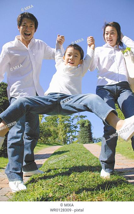 Parents lifting son