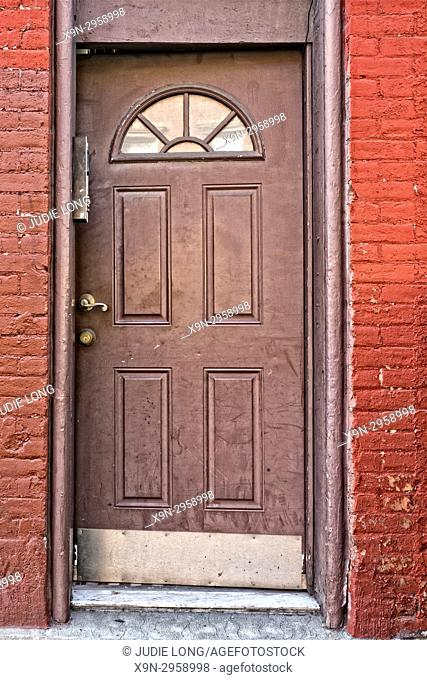 Booklyn, NY, Greenpoint. Decorative Entry Door on a Red Painted Brick Tenement Apartment Building