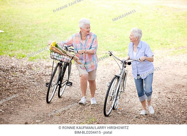 Caucasian couple walking bicycles together
