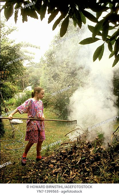 Young girl works diligently in the backyard raking up the leaves and feeding her smoky bonfire