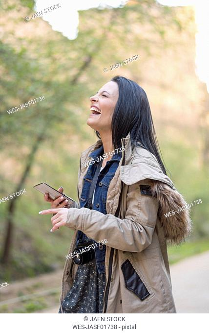 Spain, Granada, carefree young woman with camera and cell phone at the Alhambra