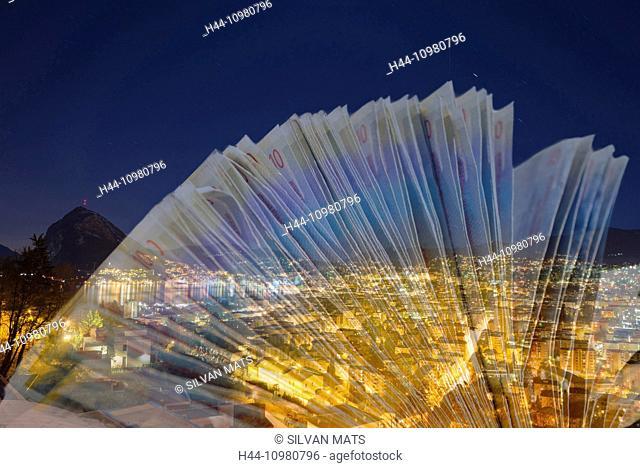 Cityscape at night with swiss francs banknotes close to a lake with mountain and with star trails in Lugano, Switzerland