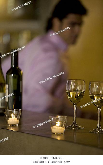 Wine glasses on candlelit bar counter