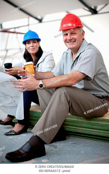 Smiling male and female construction workers sitting down holding coffee and a blueprint