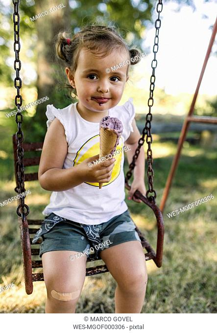 Portrait of happy little girl sitting on a swing eating ice cream