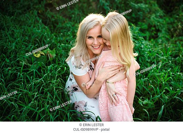 Mother and daughter in tall grass looking at camera smiling