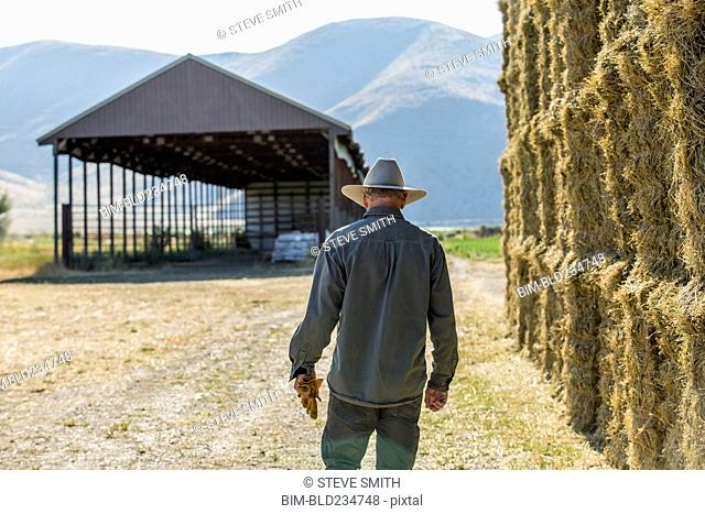 Caucasian farmer walking near stacks of hay