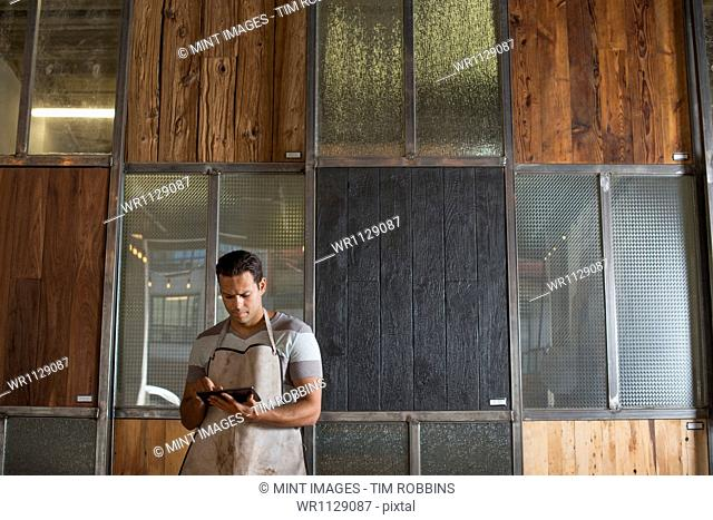A young man in a workshop which uses recycled and reclaimed lumber to create furniture and objects. Using a digital tablet to keep records and photograph...