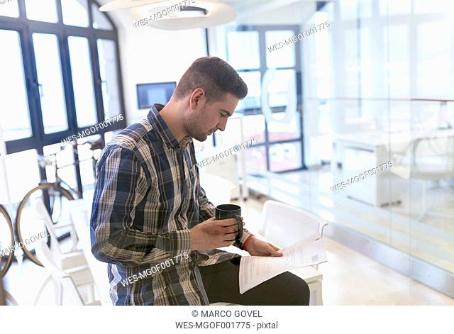 Young man in office looking at documents