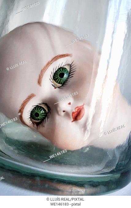 Primer plano de una cabeza de muñeca de porcelana con ojos verdes, mirando fijamente a la camara desde el interior de un bote de cristal