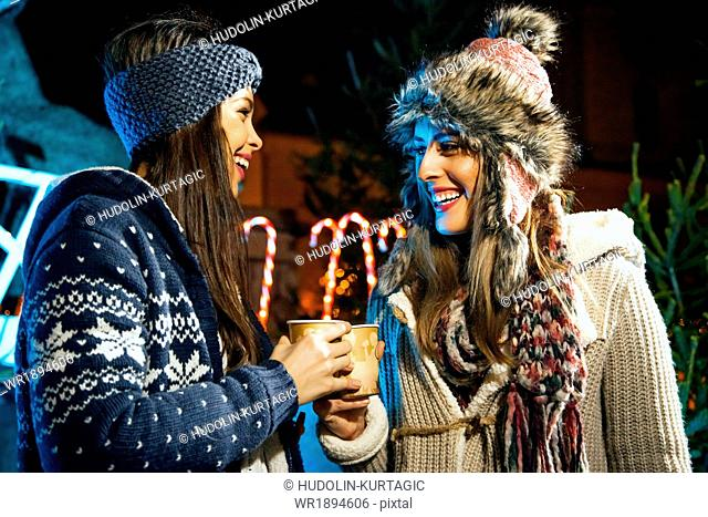 Two young women drinking punch at Christmas Market
