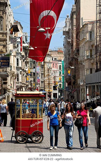 Traditional bread seller and crowds of people walking along Istiklal Caddesi beneath large Turkish flag