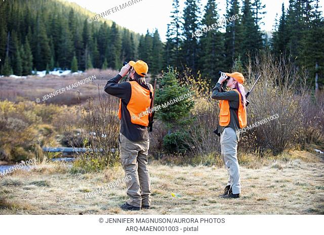 Two hunters searching for animals with binoculars, Colorado, USA