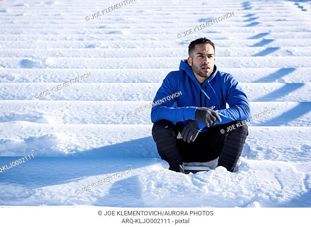 An athlete sits on snow covered stadium bench