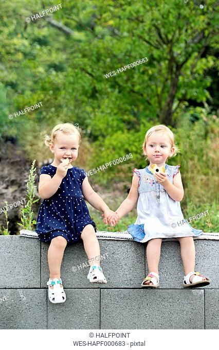 Portrait of two little sisters sitting hand in hand on a wall eating pastries