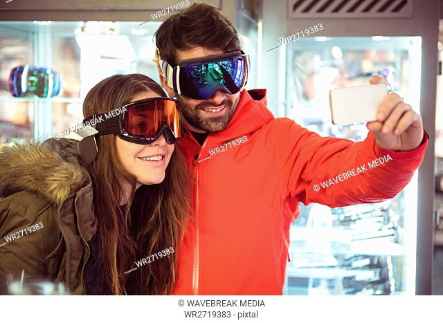 Couple in ski goggles taking a selfie
