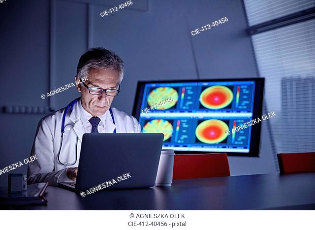 Focused male surgeon working at laptop in hospital