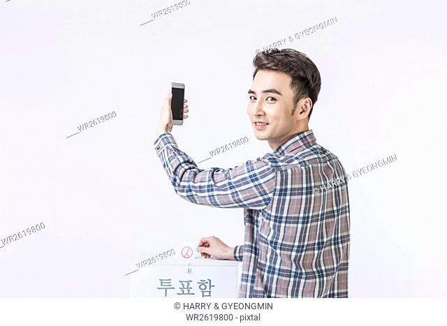 Portrait of young man with a smartphone taking a vote looking back